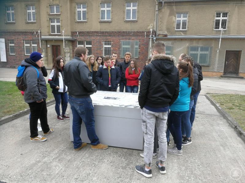Historiker André Kistner (Mitte) erläuterte den Schülerinnen und Schülern am Modell zunächst den Aufbau des ehemaligen Stasi-Gefängnisses Hohenschönhausen, bevor er ihnen Zellen und Verhörräume im Inneren der Gebäude zeigte.