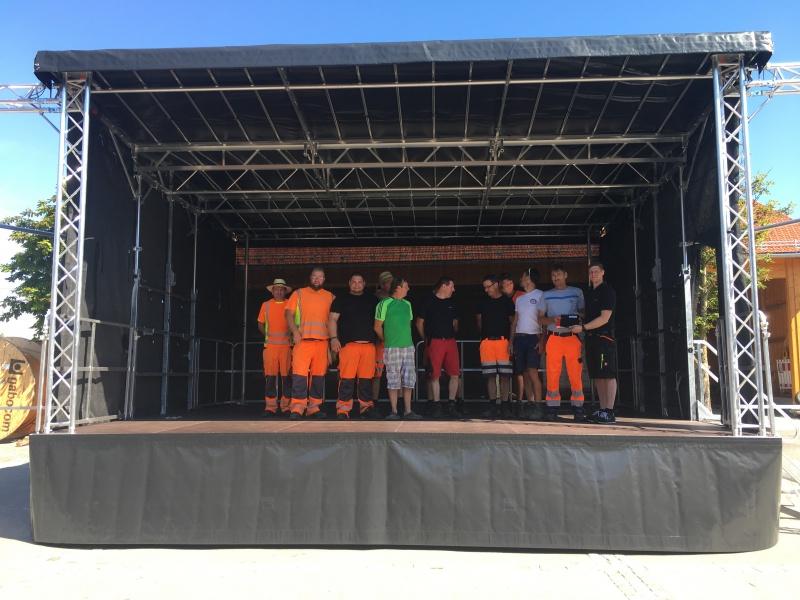 """Ein Monteur der Firma """"Stagemobil"""" zeigte den Bauhofmitarbeitern an einem Dienstagvormitag Ende Juni, wie die Bühne mit ein paar Handgriffen aufgebaut wird. So werden kommunale Ressourcen geschont und das Ehrenamt unterstützt."""