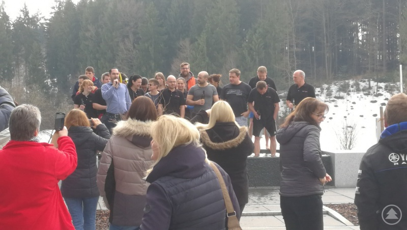 21 mutige Mitarbeiter von AVS Römer im eiskalten Brunnen. Mit Mikrofon Herr Christoph Cegla, Geschäftsführer AVS Römer GmbH