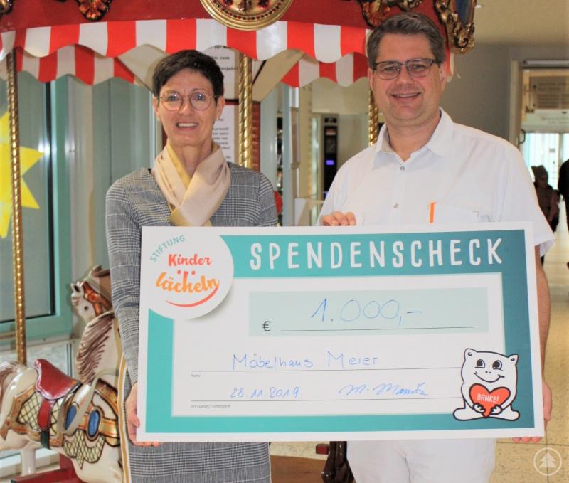 Martina Mauritz von Meier Möbel- und Raumausstattung in Untergriesbach, übergibt einen Spendenscheck in Höhe von 1.000 Euro an die Stiftung Kinderlächeln.