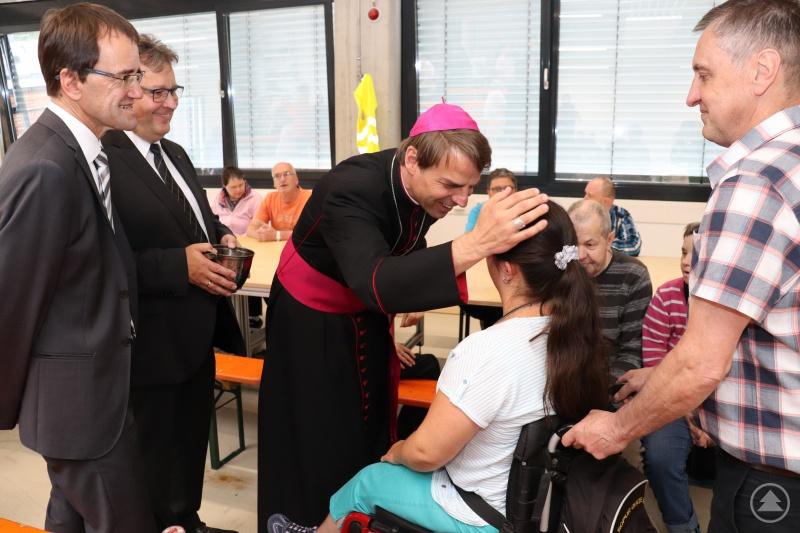 Zeit für die persönliche Begegnung. Bischof Oster spendet Lisa Bürdek den Segen. Beim Rundgang begleiten ihn die Caritasvorstände (li.) Michael Endres und Diakon Konrad Niederländer.