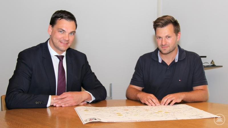 Anhand einer Karte zeigt Alexander Bauer, Leiter der Tiefbauverwaltung, Landrat Sebastian Gruber (links) noch einmal die neun Kreisstraßen-Abschnitte, die im Rahmen des diesjährigen Deckenbauprogramms saniert werden.