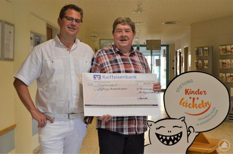 v.l. Prof. Dr. Matthias Keller nimmt im Namen der Stiftung Kinderlächeln dankend die private Spende über 300 Euro von Adolf Haberzettl entgegen.