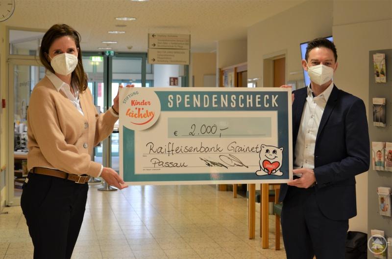 Christian Schnelzer, Vorstand der Raiffeisenbank Grainet, übergibt den Spendenscheck in Höhe von 2.000 Euro an Dr. Maria Diekmann, Vorstandsvorsitzende der Stiftung Kinderlächeln.