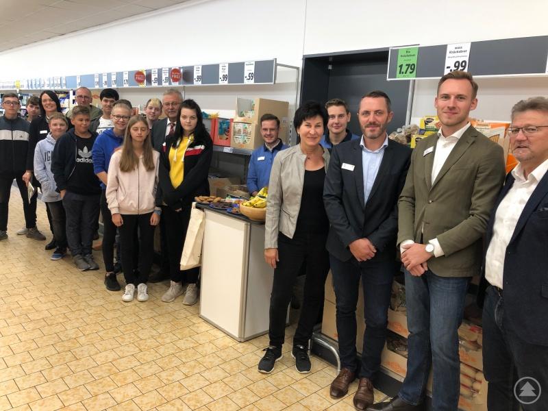 Die Schulklasse der Albertus-Schule mit Lehrer Stefan Heislbetz, Mitgliedern der Fairtrade-Steuerungsgruppe des Landkreises, Vertretern von Lidl und Landrat Josef Laumer vor dem Stand der Fairen Woche in der Lidl-Filiale Bogen-Furth.