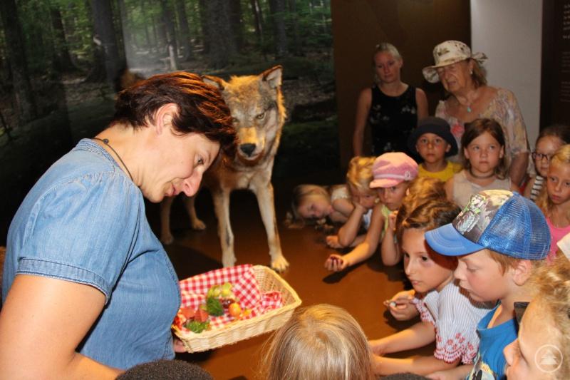 Museumspädagogin Judith Süß lässt die Kinder die passende Nahrung aus dem Fresskorb aussuchen.