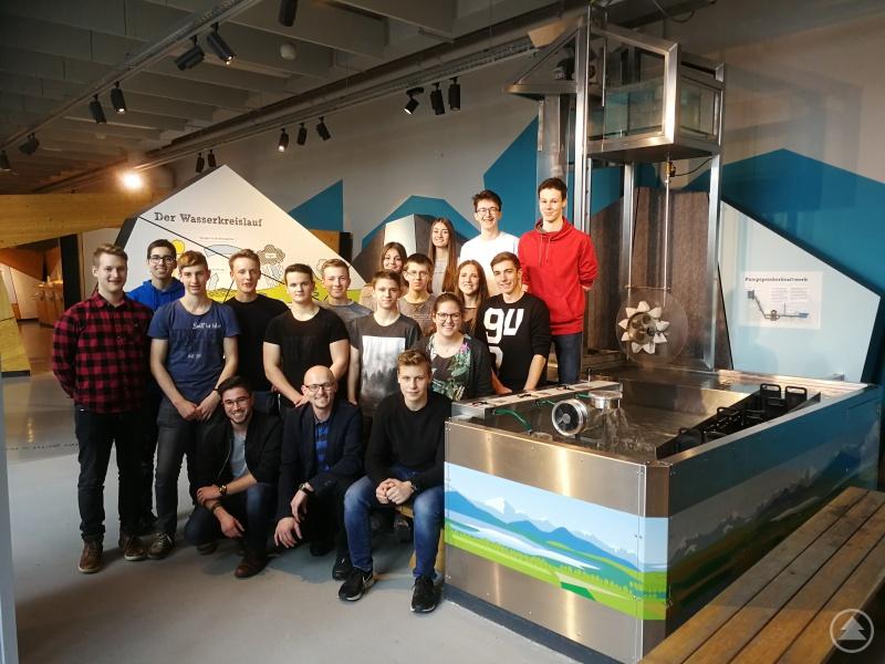 Das P-Seminar Physik unter der Leitung von Josef Müller (Mitte vorne) vor einem Modell eines Pumpspeicherkraftwerks.
