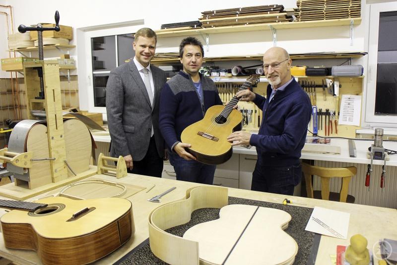 (v.l.): Bezirkstagspräsident Dr. Olaf Heinrich und Roland Pongratz, der künstlerische Leiter der Volksmusikakademie in Bayern, bedankten sich für die Gitarrenspende bei Helmuth Frisch.