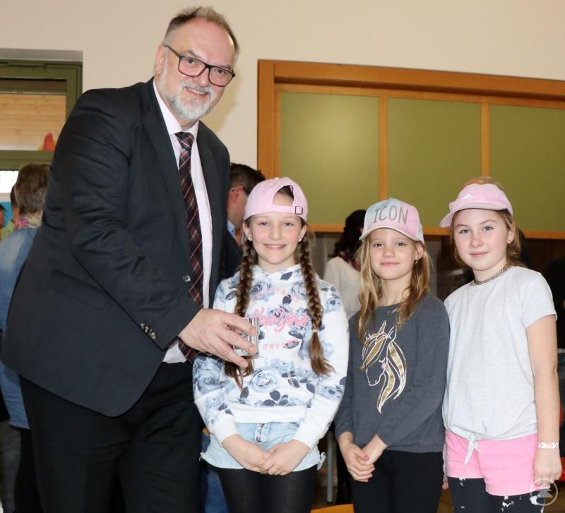 Oberbürgermeister Jürgen Dupper verteilt das Wasser vom neuen Trinkbrunnen an Schülerinnen, die bei der Einweihungsfeier mitgewirkt haben.