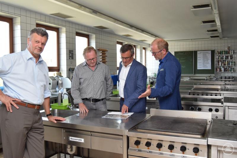 Sie begutachten die Pläne für die neuen Küchen: (von links) Schulleiter Peter Oswald, Fachpraxisleiter Johann Stubenrauch, MdL Alexander Muthmann und  Außenstellenleiter Xaver Dietrich.
