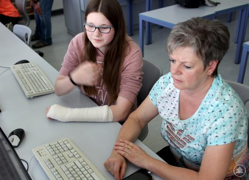 Eine Schülerin hilft einer Seniorin.