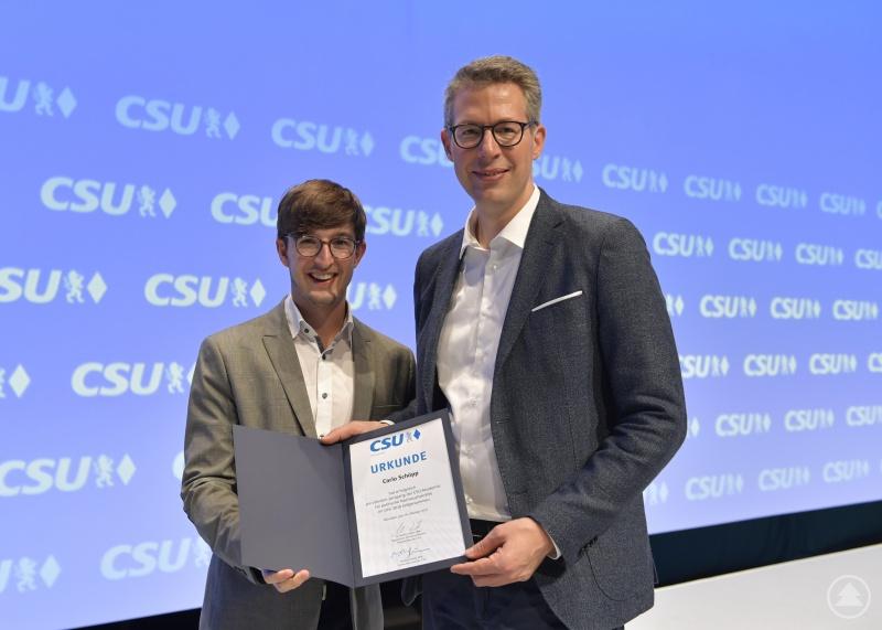 CSU-Generalsekretär Markus Blume (rechts) überreicht dem stellvertretenden JU-Kreisvorsitzenden und Schönberger Ortsvorsitzenden Carlo Schöpp (links) die Urkunde der CSU-Akademie.
