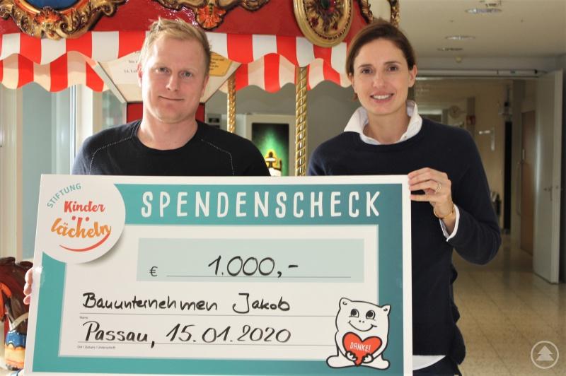 Bauunternehmer Benjamin Jakob übergibt den Spendenscheck an Dr. Maria Diekmann, Stiftungsratsvorsitzende der Stiftung Kinderlächeln.
