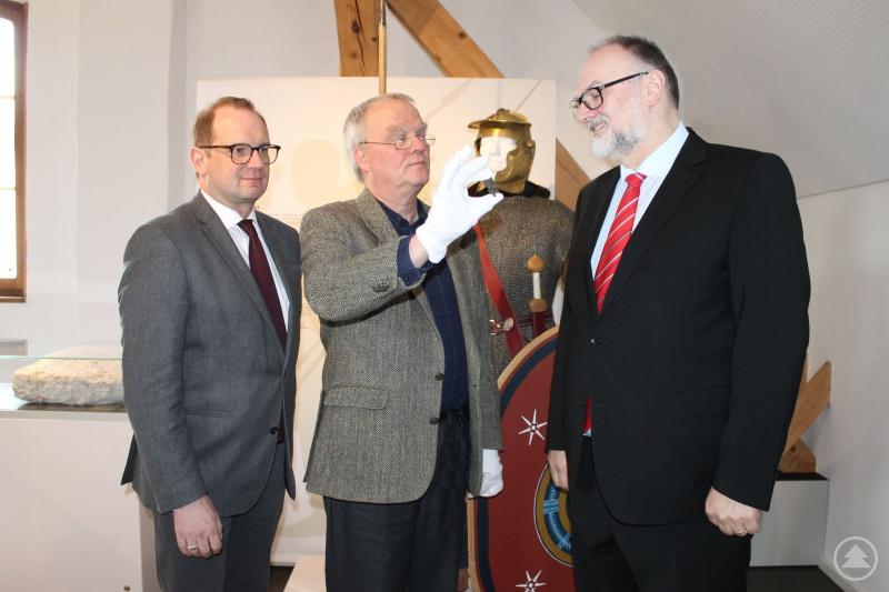 Stadtarchäologe Dr. Jörg-Peter Niemeier (Mitte) zeigt Oberbürgermeister Jürgen Dupper (rechts) und Kulturreferent Dr. Bernhard Forster eine erst kürzlich restaurierte Martis-Fibel aus der Zeit Ende 2./Anfang 3. Jahrhundert nach Christus, die im Bereich der Schlosserstiege gefunden wurde und nun im Römermuseum ausgestellt ist.