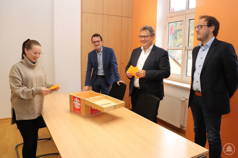 Die Auszubildende Selina Wilhelm zog die Gewinner der Restcent-Aktion. Die Caritas-Vorstände Michael Endres (v. li.) und Diakon Konrad Niederländer und der Fachbereichsleiter Personalabrechnung Patrick Lang freuten sich über die Solidarität der Mitarbeitenden.