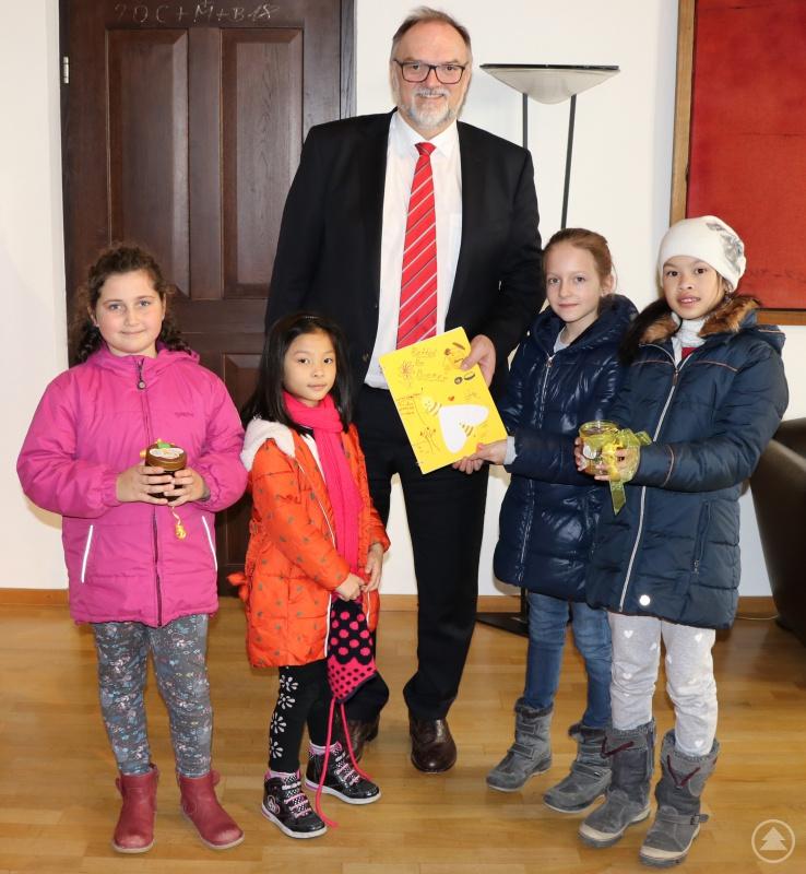 Helena (von links), Giang, Lili und Anja vom Städtischen Kinderhort übergeben stellvertretend die Unterschriftenliste und ein Glas mit echtem Imkerhonig an Oberbürgermeister Jürgen Dupper.
