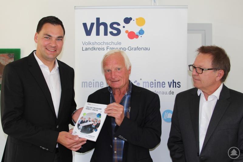 vhs-Leiter Willi Schindler (Mitte) überreicht Landrat Sebastian Gruber das erste Exemplar des neuen vhs- Semesterprogramms Herbst/Winter 2018/19. Mit auf dem Foto: vhs-Geschäftsführer Michael Dietz (rechts).