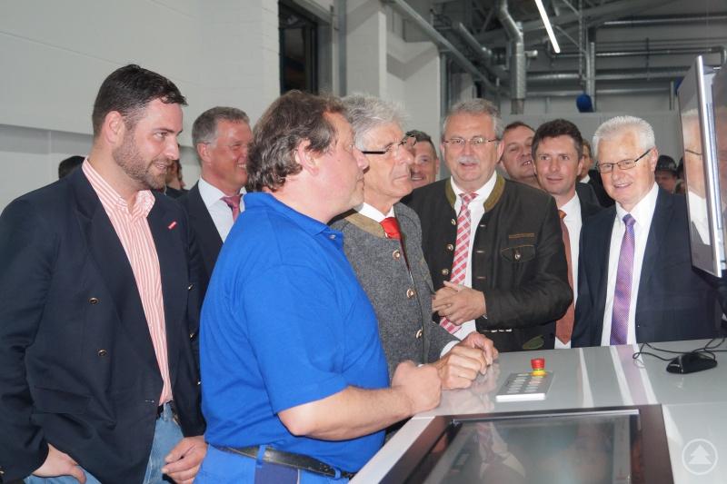 Landrat Josef Laumer (hinten, 4. von rechts) und Wirtschaftsreferent Martin Köck (ganz links) bei der Inbetriebnahme der neuen Flexodruckmaschine mit Vertretern der Firma Bischof + Klein im Werk in Konzell.