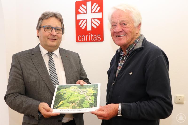 """Franz Stockinger hat mit seinem Bildband über Klingenbrunn Erfolg. Caritasvorstand Konrad Niederländer freut sich, dass der Erlös von 1000 Euro an den """"Bischof-Eder-Fond"""" geht."""