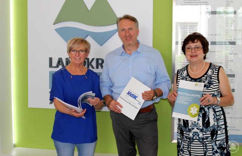 Landrätin Rita Röhrl (li.) mit Helmut Plenk sowie Christine Kreuzer und einige Notfallmappen.