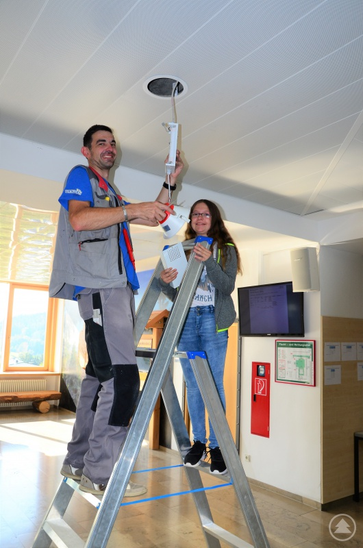 Die Realschülerin Angelina Grimm hilft bei Elektro Loibl, Grafenau, im Rahmen der Was-will-ichwerden- Woche, die Deckenbeleuchtung an der eigenen Schule zu überprüfen.