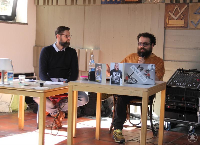 Jugendpfleger Dirk Reichel, der als Moderator fungierte, und Firat Alshater (re.) auf der Bühne in der Aula der Berufsschule Regen.