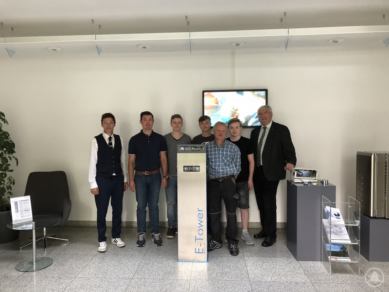 Schulleiter Günther Schwarzbauer (rechts), die Ausbilder der Sedlbauer AG (2. von links und 3. von rechts), Regionalmanager Stefan Schuster (links) und die teilnehmenden Praktikanten vor einer Sedlbauer-Ladesäule.