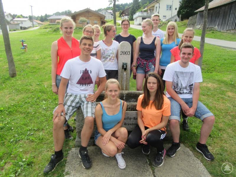 Die Projekt-Gruppe am Brunnen in der Dorfmitte Philippsreuts, einer der geplanten Stationen des von den Schülerinnen und Schülern konzipierten literarischen Rundwanderwegs in und rund um Philippsreut