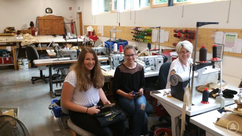 Die Schülerinnen Selina Pauli (von links) und Sophia Perl mit einer Mitarbeiterin von Trachten Freund bei der Fertigung von Lederhosen.