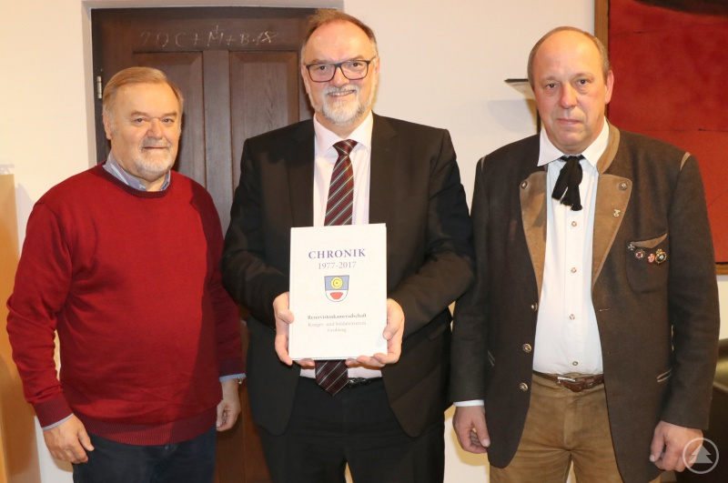 Oberbürgermeister Jürgen Dupper (Mitte) nimmt die Chronik von Reinhold Resch (links), Vorsitzender der Reservistenkameradschaft Passau-Grubweg, und Manfred Sedlacek, Vorsitzender des Krieger- und Soldatenvereins Passau-Grubweg, entgegen.