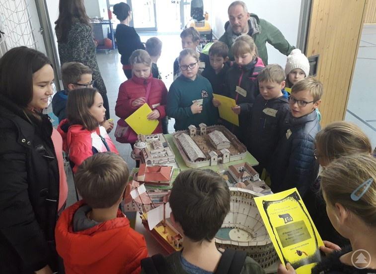 Eine der Teilnehmerinnen an P-Seminar, Anna-Lena Madl (links), erklärt den jungen Besuchern die verschiedenen Modelle antiker Bauwerke.
