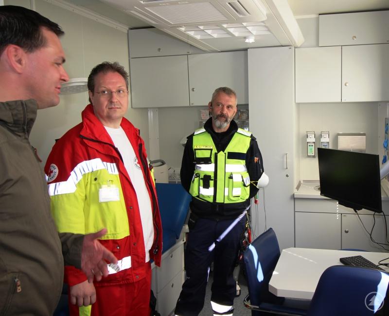 Günther Karl, Leiter Rettungsdienst BRK Freyung-Grafenau (m.), und Markus Schwarz von der Örtlichen Einsatzleitung (re.) zeigen Landrat Sebastian Gruber einen Behandlungsraum der mobilen Arztpraxis