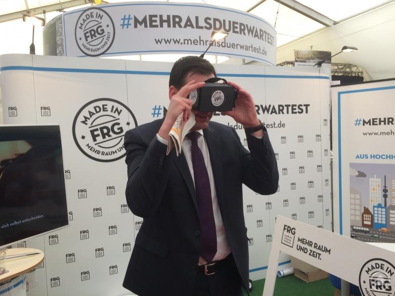Landrat Sebastian Gruber mit einer 360 Grad-Videobrille beim Betrachten eines Films über Leben in FRG.