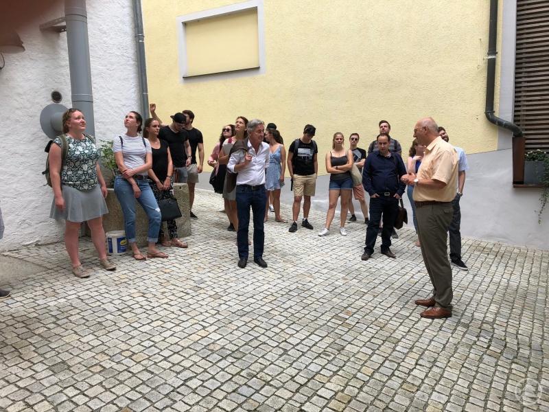 Professor Dr. Konrad Goppel, Professor für Raumordnung und Landesplanung am Institut für Geografie der Universität Augsburg (Mitte), und die an der Exkursion nach Freyung-Grafenau teilnehmenden Studierenden werden von Perlesreuts Bürgermeister Manfred Eibl (rechts) im Innenhof der Bauhütte begrüßt.