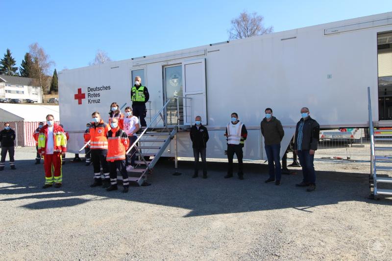 Landrat Sebastian Gruber (2. v. re.) mit weiteren Mitgliedern der Führungsgruppe Katastrophenschutz (re. Seite) und dem Team vom BRK-Kreisverband Freyung-Grafenau (Mitte) sowie der Unterstützungseinheit des DRK-Landesverbandes Baden-Württemberg (links im Hintergrund)