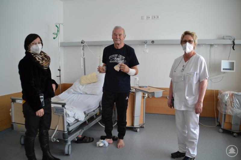 Betriebsrätin Daniela Kandlbinder (l.) und Stationsleitung der Station 1 Monika Pauli überreichen dem Patient Franz Veit das Kleeblatt und einen Engel-Anhänger