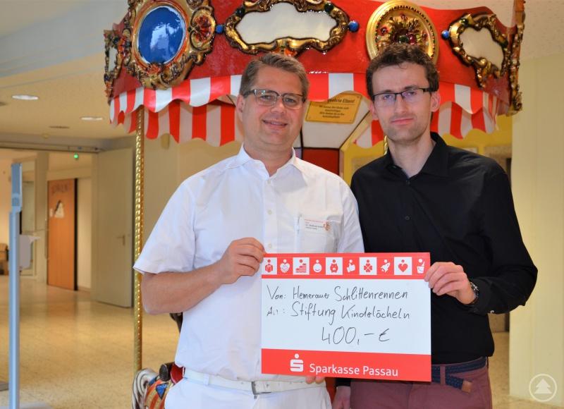 Organisator Tobias Semik (r.) übergibt den Spendenscheck über 400-Euro an die Stiftung Kinderlächeln, stellvertretend an Kinderklinik-Chefarzt Prof. Dr. Matthias Keller.