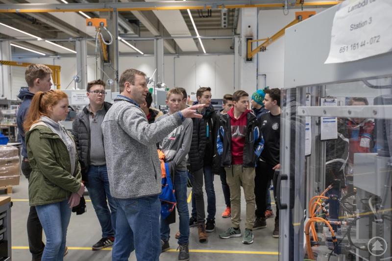 Manfred Friedl, technischer Ausbildungsleiter bei Komax, zeigt den Schülern anschaulich die Bearbeitungsschritte einer Rundtaktanlage zur Kabelverarbeitung im Bereich Sondermaschinenbau.
