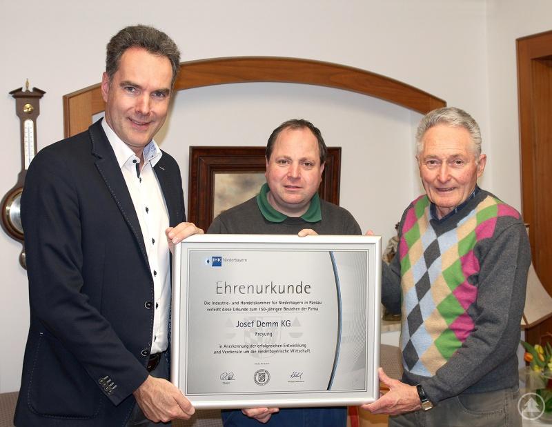 IHK-Hauptgeschäftsführer Alexander Schreiner überreichte die Ehrenurkunde an das heutige Leitungsduo Josef Demm junior und senior (von links)