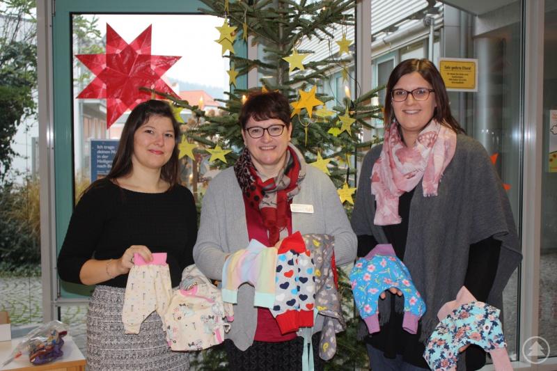 Veronika Öttl (l.) und Marina Pretzl (r.) übergeben die Babykleidung zu Gunsten kranker Kinder in der Kinderklinik an Pflegedirektorin Margit Schuster.