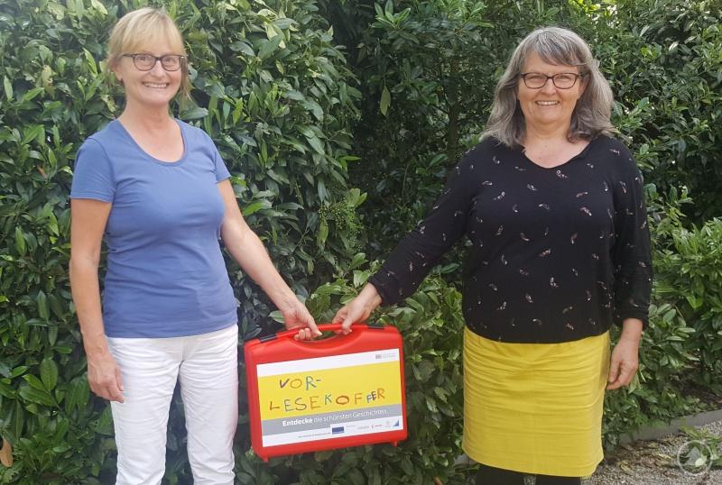 Bettina Sterzl vom Malteser-Helferkreis Salzweg (li.) freute sich über den Koffer mit Lesestoff, den Beate Heindl vom Diözesan-Caritasverband überreichte.