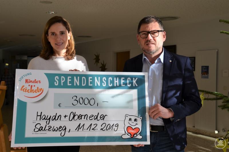 Christian Oberneder, Geschäftsführer von Haydn + Oberneder in Salzweg, übergibt einen 3.000 Euro-Spendenscheck an Dr. Maria Diekmann, Stiftungsratsvorsitzende der Stiftung Kinderlächeln.