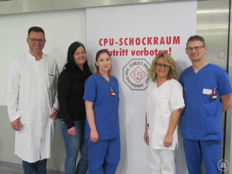 Chefarzt Peter Bomba (von links) mit Kerstin Maier, Julia Stark, Manuela Hagedorn und Manfred Stockinger vor dem neuen Logo der erfolgreich re-zertifizierten Chest Pain Unit.