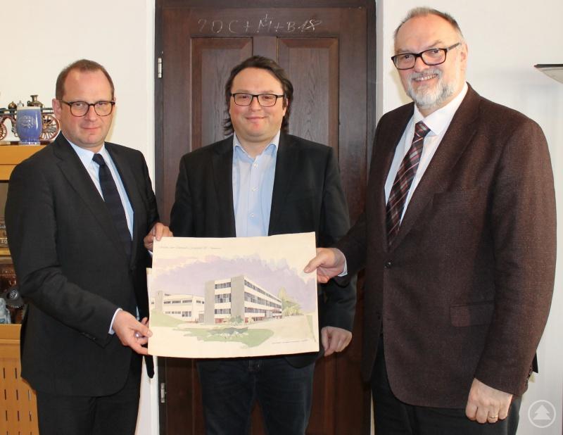 Passavia-Geschäftsführer Dominik Metzler (Mitte) übergibt das Aquarell des ehemaligen Passavia-Gebäudes in der Vornholzstraße an Oberbürgermeister Jürgen Dupper (rechts) und Kulturreferent Dr. Bernhard Forster. Es ist Teil der Schenkung an die Stadt Passau.