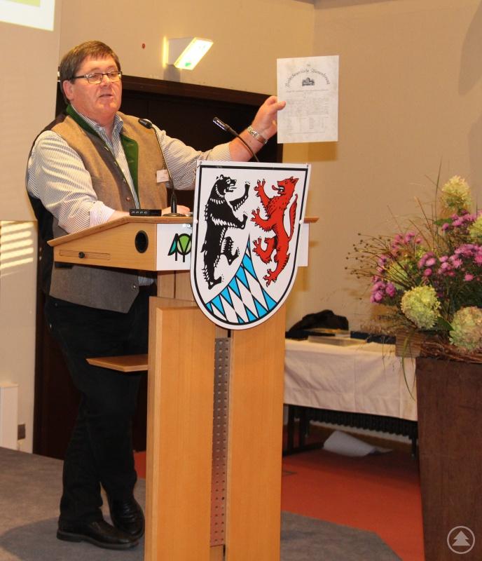 Otto Kötterl, Vorsitzender des Bezirksverbandes der Imker Niederbayern, präsentiert das historische Infoblatt der Imker aus dem Jahr 1895.