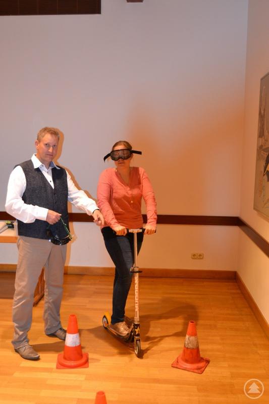 Das Bild zeigt Referent Marco Höller mit einer Besucherin, die versucht, den Parcours mit einer Rauschbrille (simuliert 1,5 Promille im Blut) zu bewältigen.