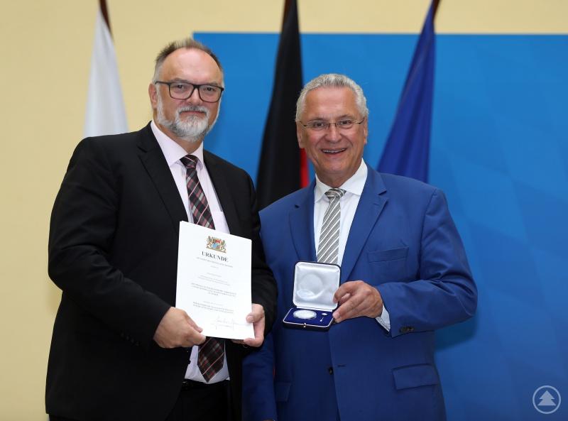 Oberbürgermeister Jürgen Dupper (links) nimmt die Auszeichnung vom Bayerischen Staatsminister des Innern, für Sport und Integration, Joachim Herrmann, in Empfang.