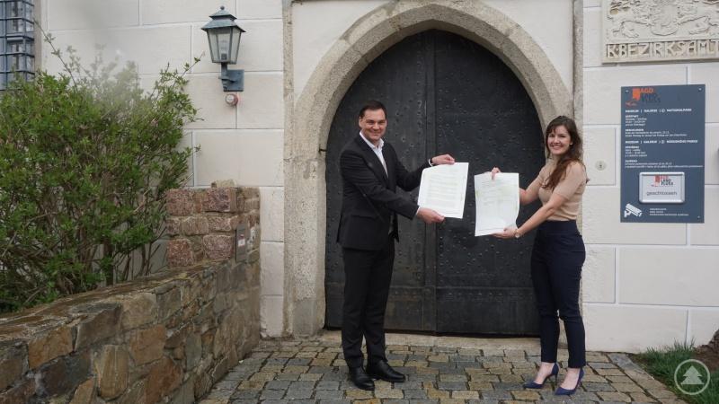 Landrat Sebastian Gruber und Klimaschutzmanagerin Verena Holzbauer zeigen die unterzeichnete Absichtserklärung zur Agenda 2030 für nachhaltige Entwicklung.