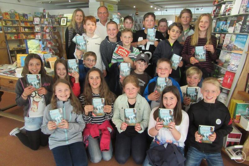 Die Klasse 5c zeigt freudig ihr Buchgeschenk in der Buchhandlung Lang