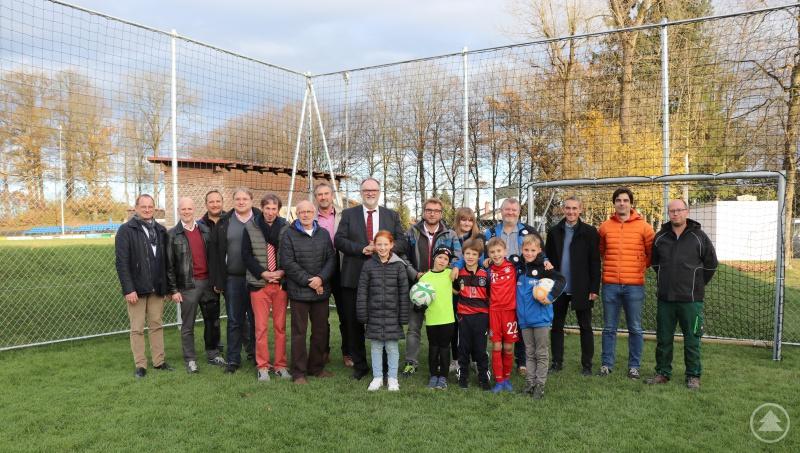 Oberbürgermeister Jürgen Dupper (8. von links) freut sich mit Vertretern des Stadtrats, der Stadtverwaltung und des VfB Passau-Grubweg über den neu angelegten Bolzplatz.